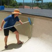 Gretel cleans calcium deposits from pool wall using an acid wash