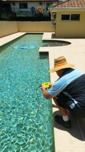 Marcus testing pool water salt content during pool maintenance service visit