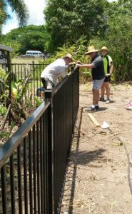 Staff finish installing a new black metal pool fence
