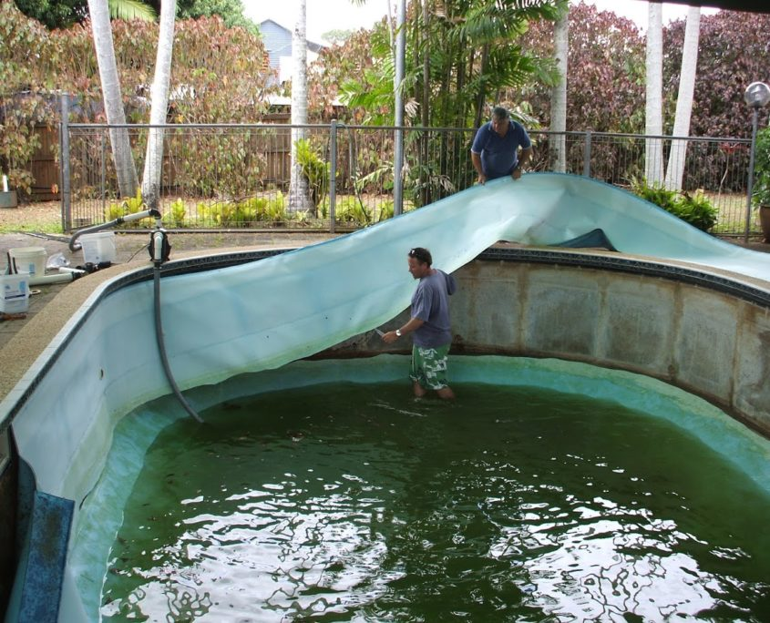 Staff remove vinyl pool liner from inground swimming pool